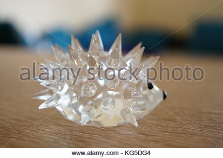 Glass hedgehog figure on wooden table - Stock Photo