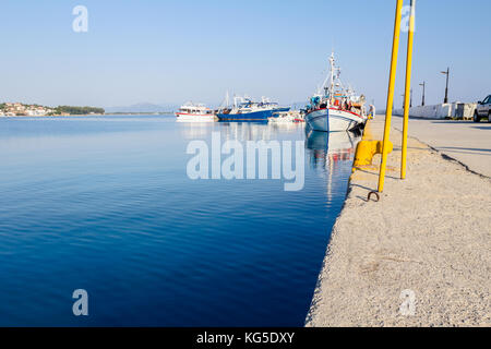 Docked colorful boats with fishing equipment are tied with ropes to the moor at the local port. - Stock Photo