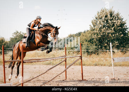 Young female jockey on horse leaping over hurdle - Stock Photo