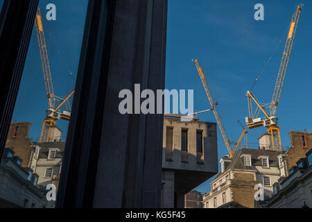 Yellow McGee Terex tower cranes work over a construction site for Edwardian Hotels near Leicester Square. - Stock Photo
