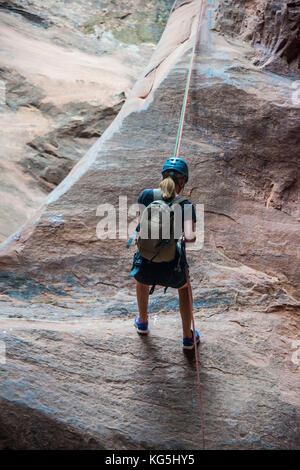 Woman rapelling down in slot canyon, Canyonering, Moab, Utah, USA - Stock Photo