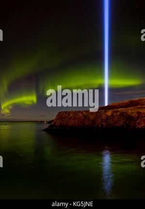 Beam of light from The Imagine Peace Tower and Aurora Borealis, Videy, Reykjavik, Iceland - Stock Photo