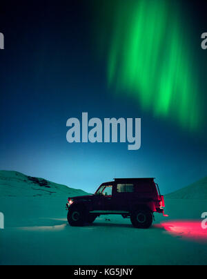 Truck in snow with Northern lights, Iceland - Stock Photo