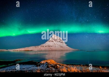 Aurora Borealis or Northern lights with the Milky Way Galaxy over fjord. Mt. Kirkjufell, Grundarfjordur, Snaefellsnes - Stock Photo