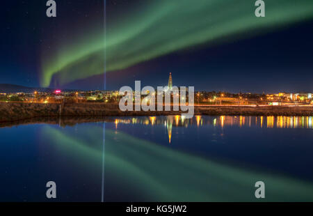 Aurora Borealis and the light beam from The Imagine Peace Tower, Reykjavik, Iceland - Stock Photo