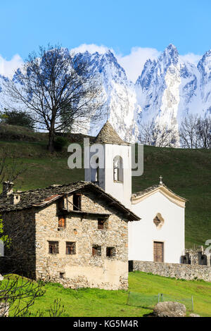 Alpine church and green meadows framed by the snowy peaks in spring Daloo Chiavenna Valley Valtellina Lombardy Italy - Stock Photo