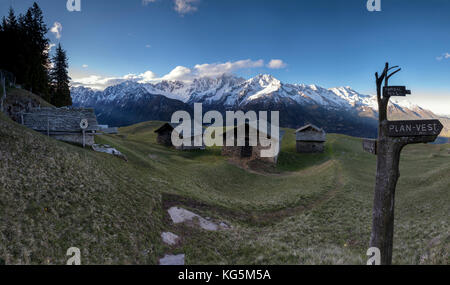 Panorama of huts and valley framed by snowy peaks at dawn Tombal Soglio Bregaglia Valley canton of Graubünden Switzerland - Stock Photo