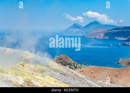 Volcano, Messina district, Sicily, Italy, Europe. Sulfur fumaroles on the crater rim of Vulcano. In the background - Stock Photo