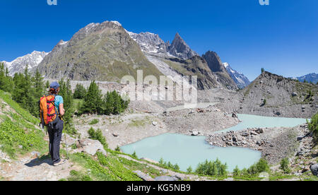 A girl looks Miage lake and Mont Blanc Massif (Miage Lake, Veny Valley, Courmayeur, Aosta province, Aosta Valley, - Stock Photo