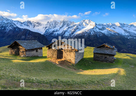 Meadows and alpine huts framed by snowy peaks at dawn Tombal Soglio Bregaglia Valley canton of Graubünden Switzerland - Stock Photo