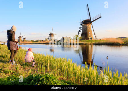 Mother and child admire the typical windmills reflected in the canal Kinderdijk Molenwaard South Holland The Netherlands - Stock Photo