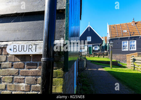A house plaque on typical brick wall in the village of Marken framed by gardens Waterland North Holland The Netherlands - Stock Photo