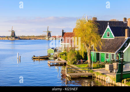Wood houses and windmill are reflected in the blue water of river Zaan Zaanse Schans North Holland The Netherlands - Stock Photo