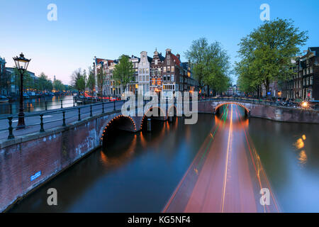 Dusk lights on the typical buildings and bridges reflected in a typical canal Amsterdam Holland The Netherlands - Stock Photo