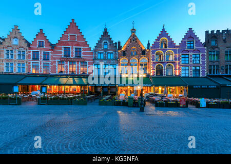 Blue lights of dusk on the colorful medieval houses in Market Square Bruges West Flanders Belgium Europe - Stock Photo