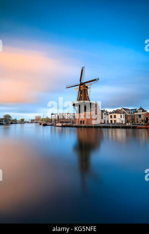 Pink clouds at sunset on the Windmill De Adriaan reflected in river Spaarne Haarlem North Holland The Netherlands - Stock Photo
