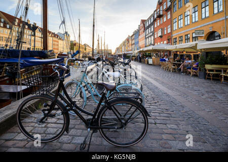 Bicycles and typical restaurants in the waterfront entertainment district of Nyhavn, Copenhagen, Denmark, Europe - Stock Photo