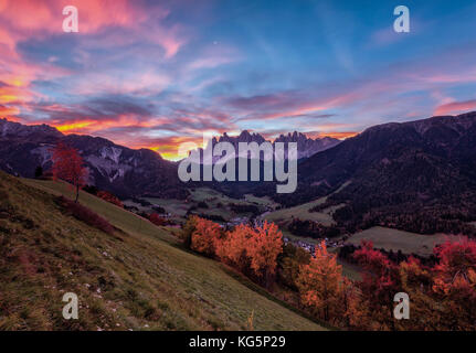 Colorful autumn trees frame the group of Odle and the village of St. Magdalena at dawn Funes Valley South Tyrol - Stock Photo