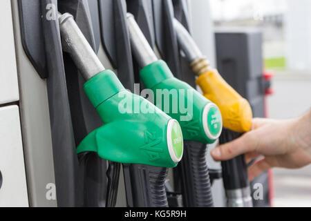 Gas filling nozzles (guns) at a gas station. - Stock Photo