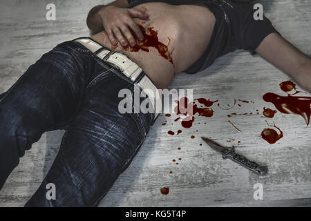 A victim of a violent crime lies in an apartment. The Young man's body in a bloody wound lying on the dirty floor - Stock Photo