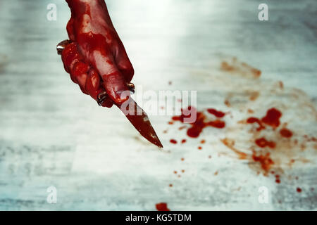 Male hand with bloody knife against the white floor with puddles of blood. Stabbing. Kill with a knife. - Stock Photo