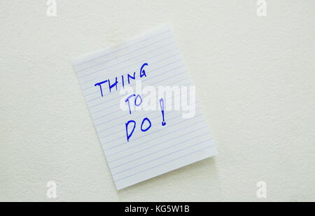 paper write thing to do stick on the white wall - Stock Photo