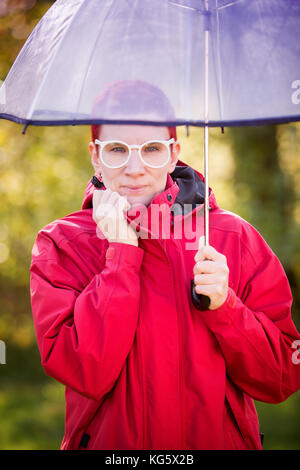 portrait of woman with red coat under transparent umbrella - Stock Photo