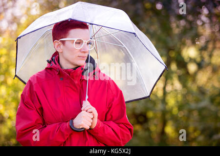 portrait of red-haired woman in red coat with umbrella - Stock Photo
