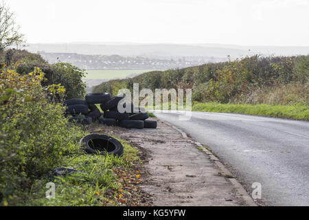 fly tipping of tyres by the side of a rural road just outside the village of Barnburgh, Doncaster, South Yorkshire, England, UK
