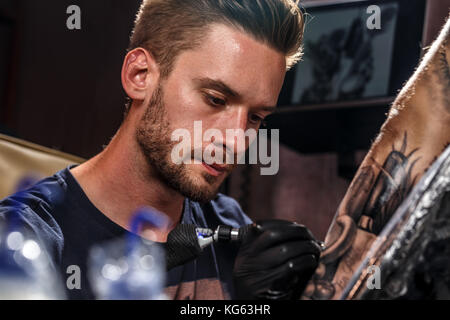 Professional tattoo artist at work in a tattoo studio. - Stock Photo