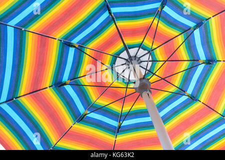 beach umbrellas with rainbow colors, open to protect from the sun - Stock Photo