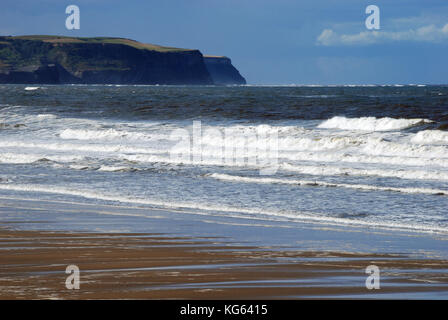 Small white capped waves breaking over a sandy beach with the silhouette of a large headland in the background - Stock Photo