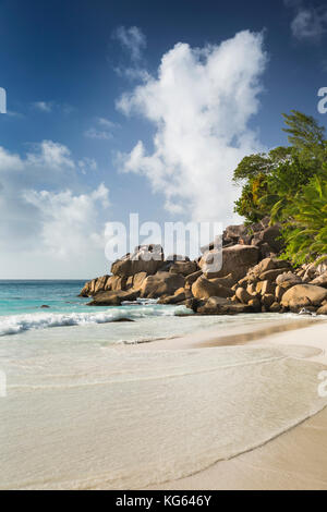 The Seychelles, Praslin, Anse Georgette, beach man sat on rocks at edge of beach - Stock Photo