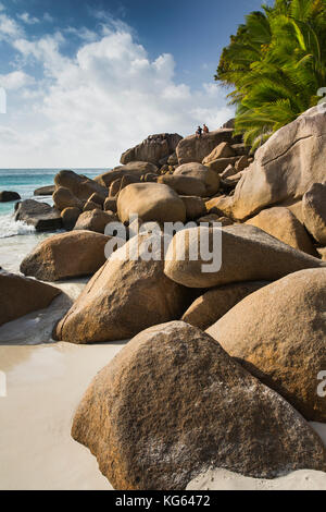 The Seychelles, Praslin, Anse Georgette, beach couple sat on rocks at edge of beach - Stock Photo