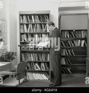 1960s, historical, administration, a male office worker checking paperwork from filing cabinets in an office. - Stock Photo