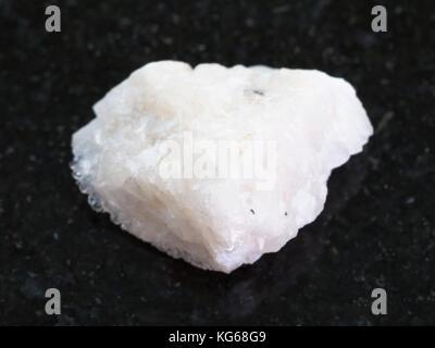 macro shooting of natural mineral rock specimen - rough Barite stone on dark granite background - Stock Photo