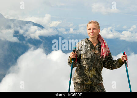 hiker woman in the background of a highland landscape and clouds - Stock Photo