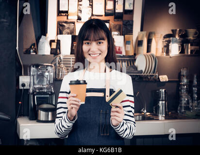 Woman barista holding coffee to go cup and credit card,asia female waitress using contactless payment in coffee - Stock Photo