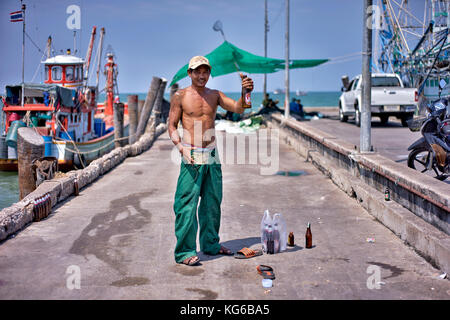 Thailand dock worker enjoying a beer after a hard days work, - Stock Photo