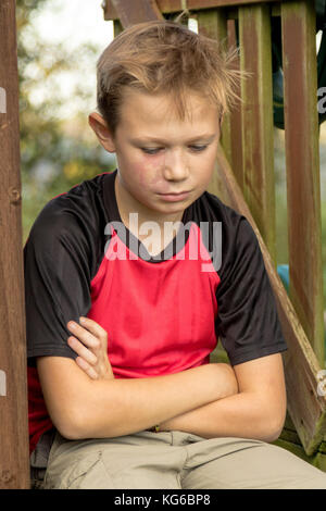 Sad pre-teen boy sitting outside on a climbing frame - Stock Photo