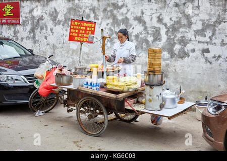 Lijiang, Yunnan, China - September 27, 2017: Woman prepares and sells breakfast food from street stall. Payment - Stock Photo