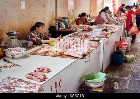 Lijiang, Yunnan, China - September 27, 2017: Women sell fresh meat at the local market. - Stock Photo