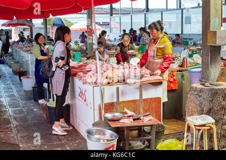 Lijiang, Yunnan, China - September 27, 2017: Customer chooses fresh meat at the local market. - Stock Photo