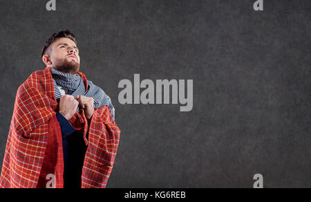 A sick man in a blanket.  - Stock Photo