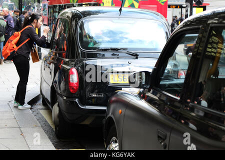 Hailing a traditional Black Cab in London outside Selfridges on Oxford Street Central London UK - Stock Photo
