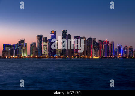 Qatar. Doha skyscrapers with external lighting. Cloudless sky and sunset - Stock Photo