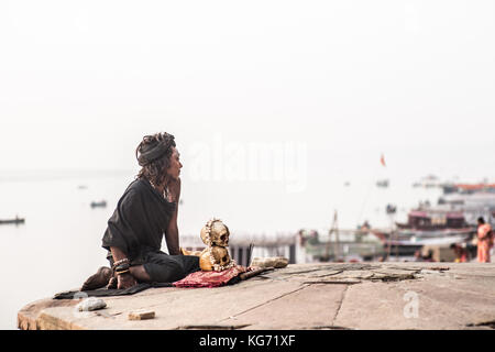 An Agori-yogi (hindu devotee) sitting with his human skulls next to the holy Ganges river and praying in the sunrise. - Stock Photo