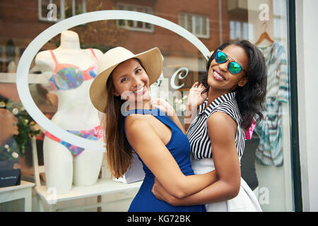 Two playful chic young women enjoying a day out together shopping turning arm in arm to smile at the camera in front - Stock Photo