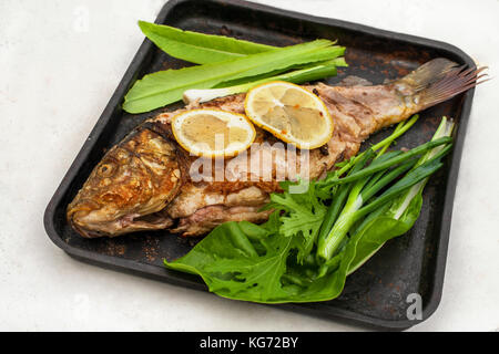Baked carp marinated in lemon and spices with green leaf lettuce on a light wooden background. - Stock Photo