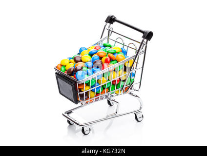 Round coated sweet candies in shopping cart on white background - Stock Photo